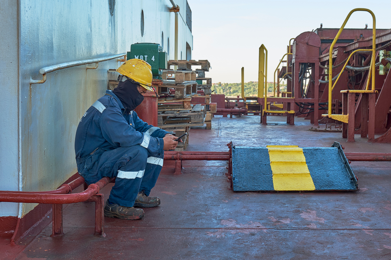 seafarer sits alone on the deck of a rusty looking ship, wearing protective clothing for his job